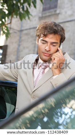 Businessman using a cell phone to make a phone call while standing by some cars in the city. - stock photo