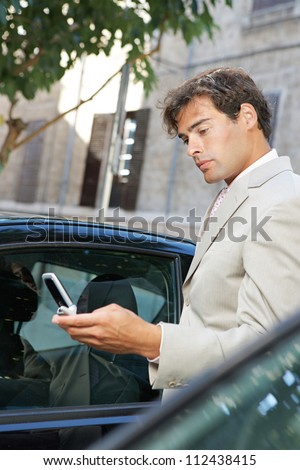 Businessman using a cell phone to send a message while standing by some cars in the city.