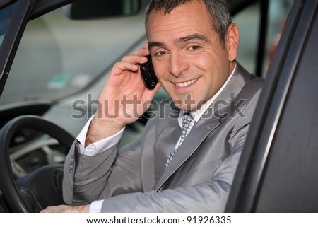 Businessman using a cellphone in his car - stock photo