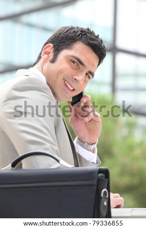 Businessman using a cellphone outside - stock photo