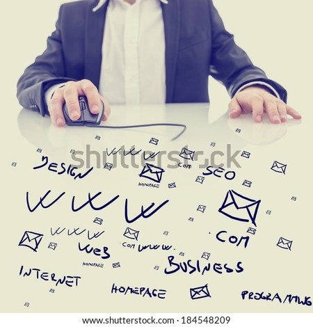 Businessman using a computer mouse sitting at a glass topped desk covered in hand-drawn computing, business and e-commerce icons and notations in a conceptual image. With retro filter effect. - stock photo