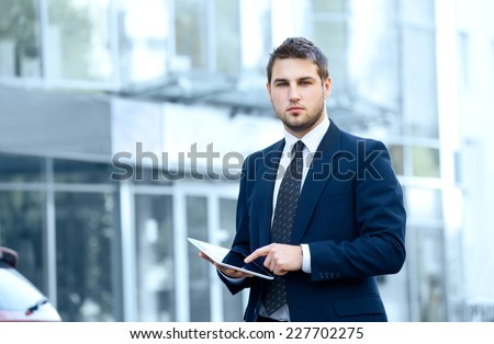 Businessman using a digital tablet computer, standing in front of his office. - stock photo