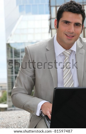 Businessman using a laptop computer outside - stock photo