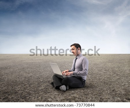 Businessman using a laptop in a desert - stock photo