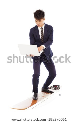 businessman using a laptop on a  surfboard  - stock photo