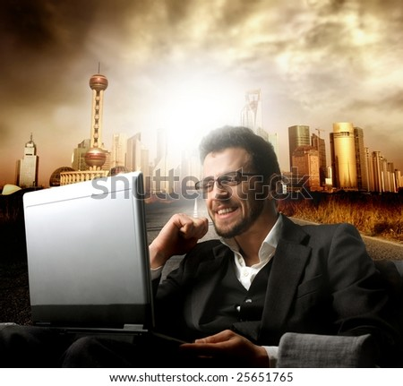 businessman using a laptop on cityscape background - stock photo