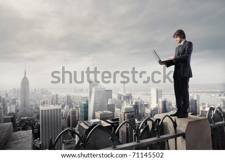 Businessman using a laptop on the rooftop of a skyscraper - stock photo