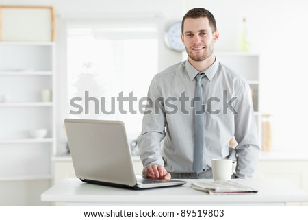 Businessman using a laptop while drinking tea in his kitchen - stock photo