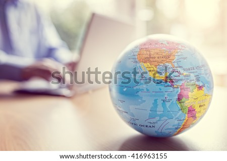 Businessman using a laptop with close up on world globe - stock photo