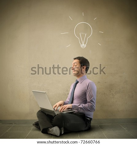 Businessman using a laptop with light bulb over his head - stock photo