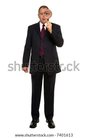 Businessman using a magnifying glass for a close inspection. - stock photo