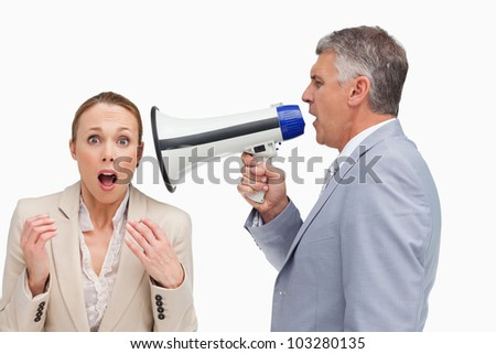 Businessman using a megaphone after his colleague against white background