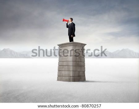 Businessman using a megaphone from a tower in the desert - stock photo