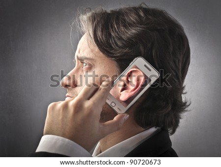 Businessman using a mobile phone with an ear on its screen