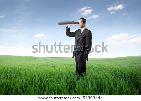 Businessman using a paper tube as binocular - stock photo