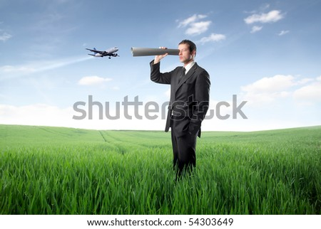 Businessman using a paper tube as binocular and plane on the background - stock photo