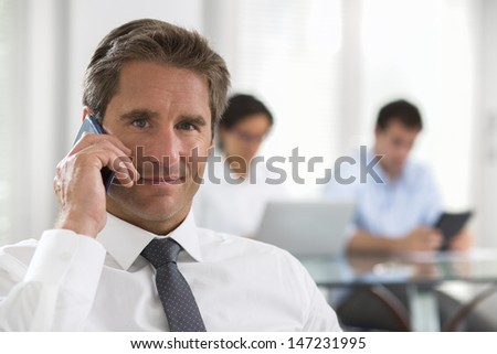 Businessman using a smartphone during a meeting  - stock photo