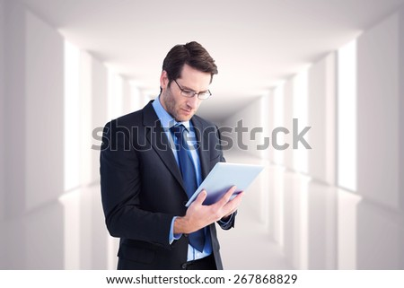 Businessman using a tablet computer against digitally generated room - stock photo