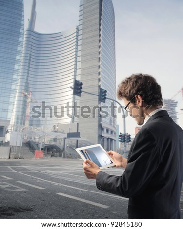 Businessman using a tablet pc on a city street - stock photo