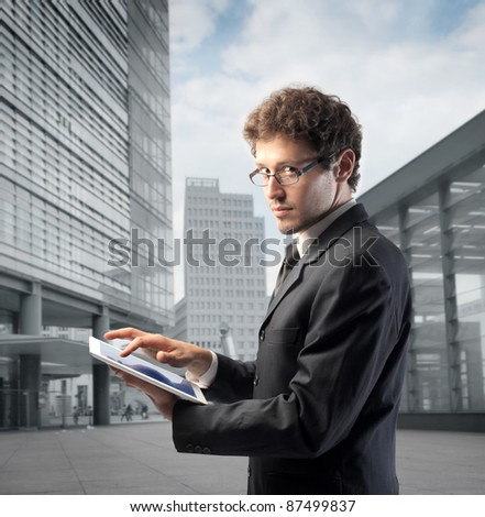 Businessman using a tablet pc with office buildings in the background - stock photo