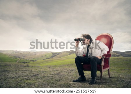 Businessman using binoculars  - stock photo