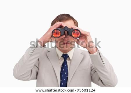 Businessman using binoculars against a white background - stock photo