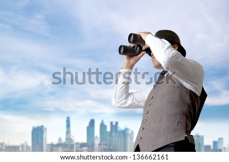 Businessman using binoculars looking for something.