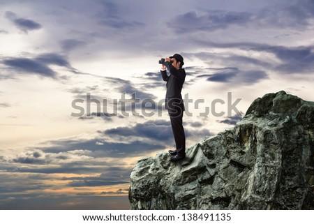 Businessman using binoculars looking for something. - stock photo