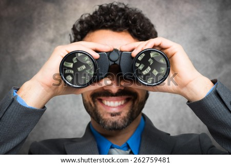 Businessman using binoculars, money reflected in the lens - stock photo