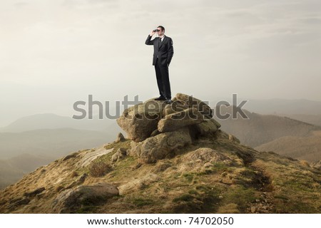 Businessman using binoculars on a rock in the mountains - stock photo