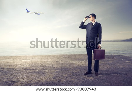 Businessman using binoculars with airplane in the background - stock photo