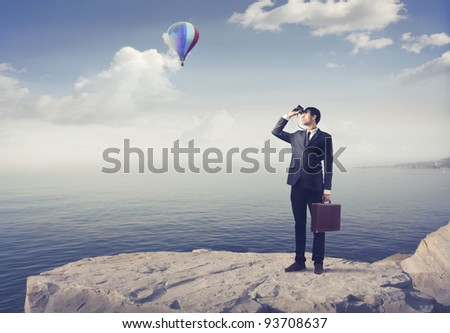 Businessman using binoculars with hot-air balloon in the background - stock photo