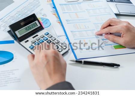 Businessman using calculator analyze report - stock photo