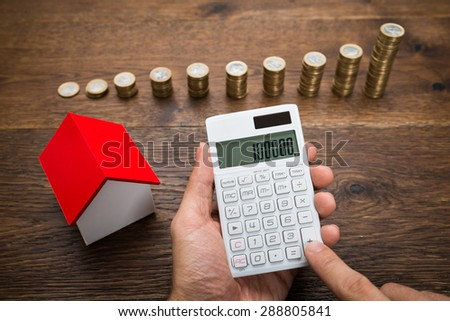 Businessman Using Calculator With House Model And Stack Of Coins On Desk - stock photo
