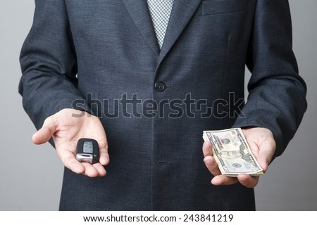 Businessman using car key and money. Keyless in male hand