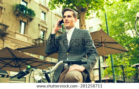 Businessman Using Cell Phone While Sitting On Bicycle - stock photo