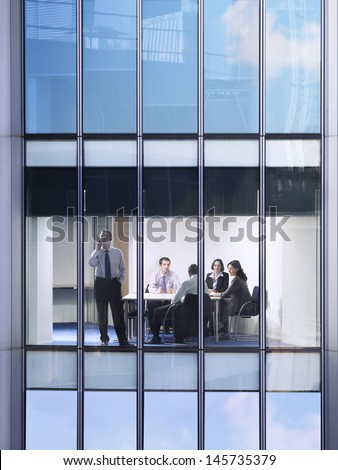 Businessman using cellphone with colleagues discussing at conference table - stock photo
