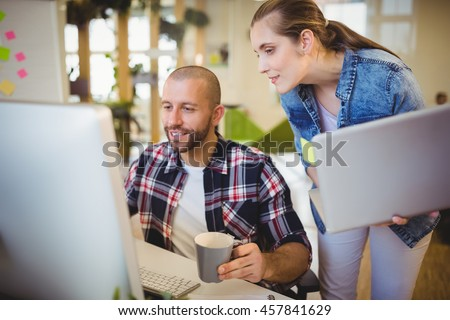 Businessman using computer while working with female colleague in creative office - stock photo