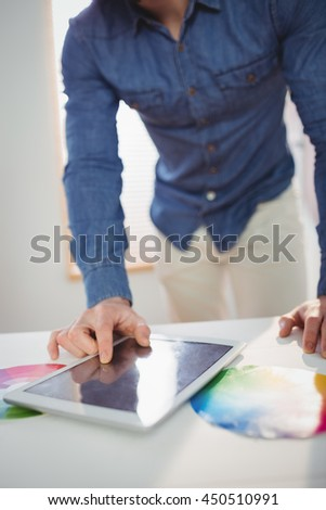 Businessman using digital tablet at office - stock photo