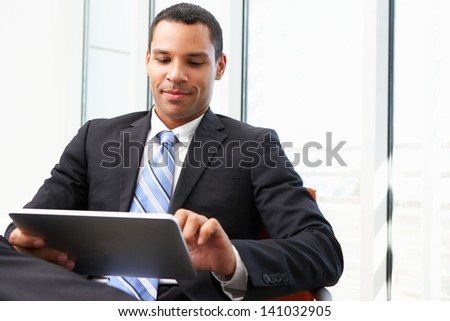 Businessman Using Digital Tablet In Office - stock photo