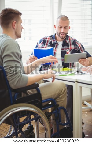 Businessman using digital tablet while discussing with handicap colleague in creative office