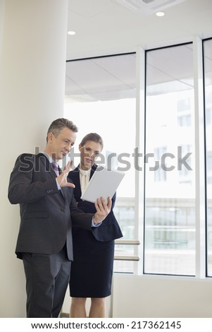 Businessman using digital tablet with female colleague in office - stock photo