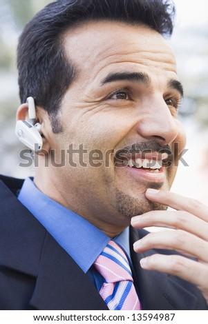 Businessman using earpiece outside - stock photo