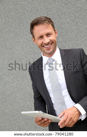 Businessman using electronic tablet leans against wall - stock photo