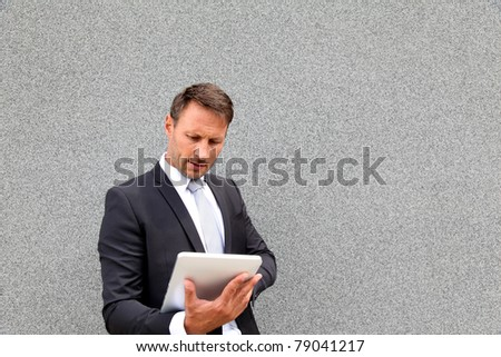 Businessman using electronic tablet leant against wall - stock photo