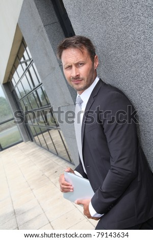 Businessman using electronic tablet outside offices building - stock photo