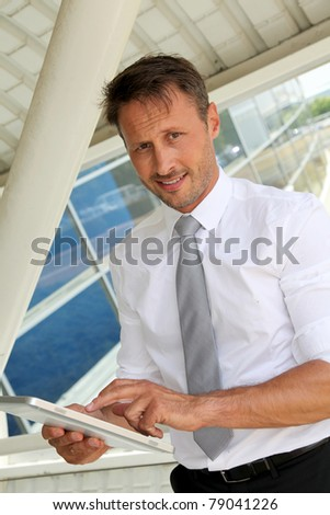 Businessman using electronic tablet outside the airport - stock photo