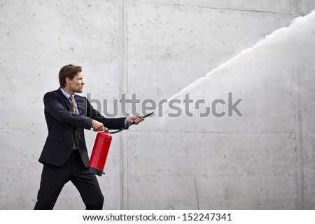 Businessman using fire extinguisher at a target as if controlling damage or problems - stock photo