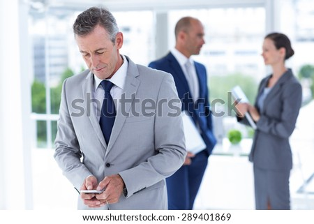 businessman using her phone with two colleague behind him at the office