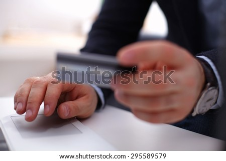 Businessman using his credit card for an online transaction,Businessman using his credit card for an online transaction